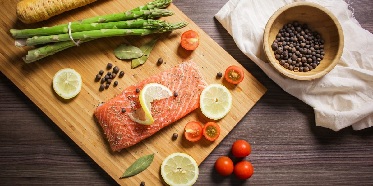 Board with fresh salmon, asparagus and spices